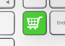 Значок магазинной тележкаи на зеленой кнопке клавиатуры Стоковые Фото