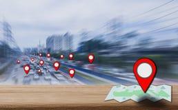 Значок указателя карты установил на деревянном столе, предпосылка запачканные улицы и затор движения города, с концепцией использ стоковая фотография rf