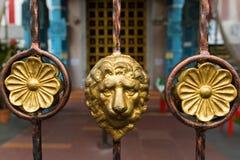 Золотая голова льва на загородке металла украшая на виске veeramakaliamman Sri, Сингапуре стоковые фотографии rf