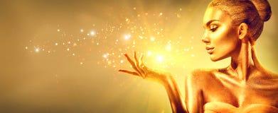Золотая женщина с подарком рождества волшебным Девушка фотомодели красоты с золотым макияжем, волосами и украшениями стоковые фотографии rf