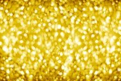 Золотая запачканная сияющая предпосылка bokeh, defocused желтый цвет сверкнает фон, пузыри круга цвета золота запачкает влияние,  стоковое фото rf