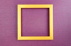Золотая квадратная рамка на nacreous пурпурной бумажной предпосылке стоковое изображение