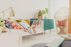 Золотая лампа на nightstand в спальне девушки boho с красочными постельными принадлежностями на кровати, зеленом деревянном шкафе стоковое изображение rf