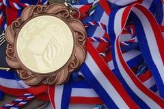 Золотая медаль с покрашенными лентами, синью, белизной и красным цветом Марианна французский символ на медали стоковые фото