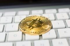 Золотая монета Bitcoin на клавиатуре компьютера стоковые фотографии rf