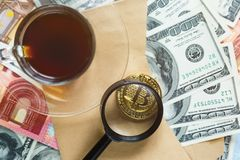 Золотая монетка валюты Bitcoin секретная на долларе, предпосылке банкнот евро и кредитной карточке около чашки кофе облечения стоковое изображение rf