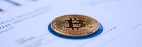 Золотая монетка знака btc лежа на крупном плане диаграммы stats Стоковое Изображение