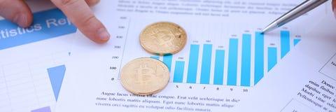 Золотая монетка знака btc лежа на крупном плане диаграммы stats Стоковая Фотография RF
