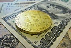 Золотая монетка bitcoin на долларах США закрывает вверх стоковое фото