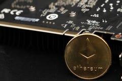 Золотая монетка ethereum с графической карточкой стоковые фото