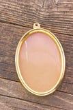 Золотая овальная рамка на деревянной предпосылке Стоковое фото RF