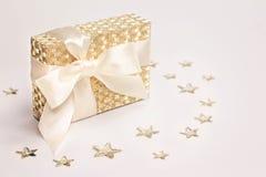 Золотая присутствующая коробка со смычком сатинировки на белой предпосылке украшенной с сияющими звездами скопируйте космос стоковая фотография