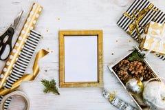Золотая рамка ptoto, подарочные коробки, клеть вполне конусов сосны и игрушек рождества и оборачивая материалов на белом деревянн Стоковое Изображение