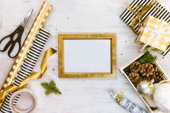 Золотая рамка ptoto, подарочные коробки, клеть вполне конусов сосны и игрушек рождества и оборачивая материалов на белом деревянн Стоковые Изображения RF