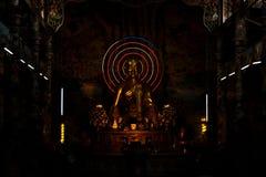 Золотая сидя статуя Будды в темноте азиатской святыни Стоковые Изображения