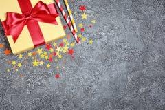 Золотая сияющая классическая подарочная коробка с красными соломами коктеиля смычка и бумаги сатинировки с confetti в форме звезд стоковая фотография