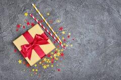 Золотая сияющая классическая подарочная коробка с красными соломами коктеиля смычка и бумаги сатинировки с confetti в форме звезд стоковое фото rf