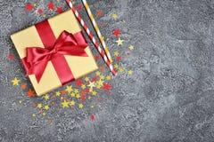 Золотая сияющая классическая подарочная коробка с красными соломами коктеиля смычка и бумаги сатинировки с confetti в форме звезд стоковое фото
