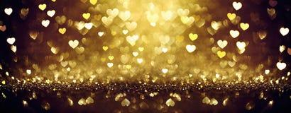 Золотая сияющая предпосылка с сердцами стоковое фото