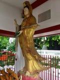 Золотая скульптура женщины около tamachat Wat, тайского виска Бангкок стоковое изображение