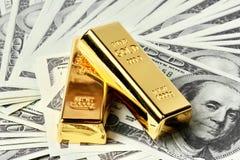 2 золота в слитках и много из банкноты Стоковые Изображения