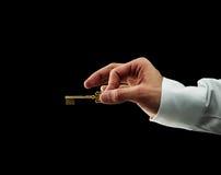 золотистая рука держа людской ключа Стоковые Фотографии RF