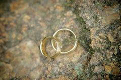 Золотистые обручальные кольца на камне Стоковые Изображения RF