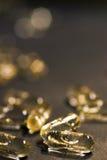 золотистые пилюльки Стоковые Изображения