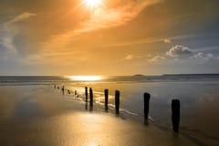 Золотистый восход солнца над выключателями пляжа стоковое фото