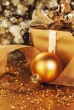 Золотистый шарик рождества около подарка на рождество Стоковые Изображения RF