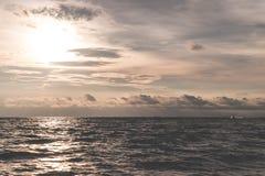 Золотое драматическое небо океана при отраженное солнце Стоковые Фото
