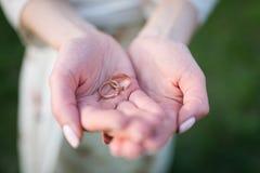 Золотое обручальное кольцо и обручальное кольцо в руках женщины Стоковое Фото