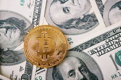 Золотое bitcoin как самое важное cryptocurrency всемирно с 100 банкнотами доллара на предпосылке Стоковое Изображение