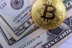 Золотое Bitcoin лежит на банкнотах американские доллары Он-лайн принципиальная схема дела стоковые фото