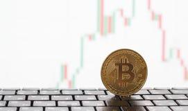 Золотое bitcoin на клавиатуре, на заднем плане белая диаграмма цен роста и понижаться стоковая фотография