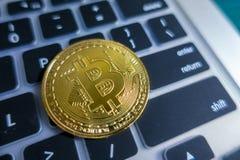 Золотое Bitcoin на клавиатуре компьтер-книжки при палец указывая дальше входит в Стоковое Фото