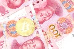 Золотое bitcoin на куче 100 китайских bac банкнот юаней Стоковые Фотографии RF