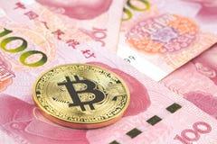 Золотое bitcoin на куче 100 китайских bac банкнот юаней Стоковые Фото