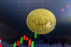 Золотое Bitcoin на черном экране компьтер-книжки с диаграммой фондовой биржи Стоковые Фотографии RF