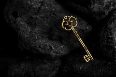 Золотой античный ключ на черной каменной предпосылке стоковые фото