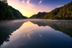 Золотой блеск солнца на зеленых деревьях на холме, отражении на спокойном озере, под голубым небом и золотым красочным облаком стоковая фотография