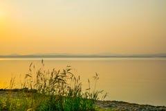 Золотой заход солнца на береге озера с силуэтом заводов, Uveldy, Ural, Россией Стоковое Фото