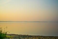 Золотой заход солнца на береге озера с силуэтом заводов, Uveldy, Ural, Россией Стоковые Фото