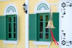 Золотой колокол виска против зеленого окна Стоковые Изображения