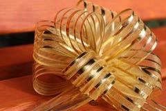 Золотой праздничный конец-вверх смычка на деревянной предпосылке стоковая фотография rf