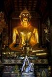 Золотой сияющий Будда в темном виске Стоковое Фото