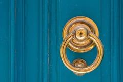 Золотой knocker двери на голубой деревянной двери Стоковое Фото