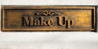 Золото выбило помечать буквами макияж на белой стене стоковая фотография rf
