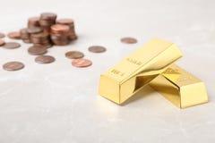 Золото в слитках и монетки на таблице стоковое фото