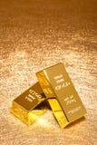 Золото в слитках на сияющей золотой вертикали предпосылки стоковые изображения rf